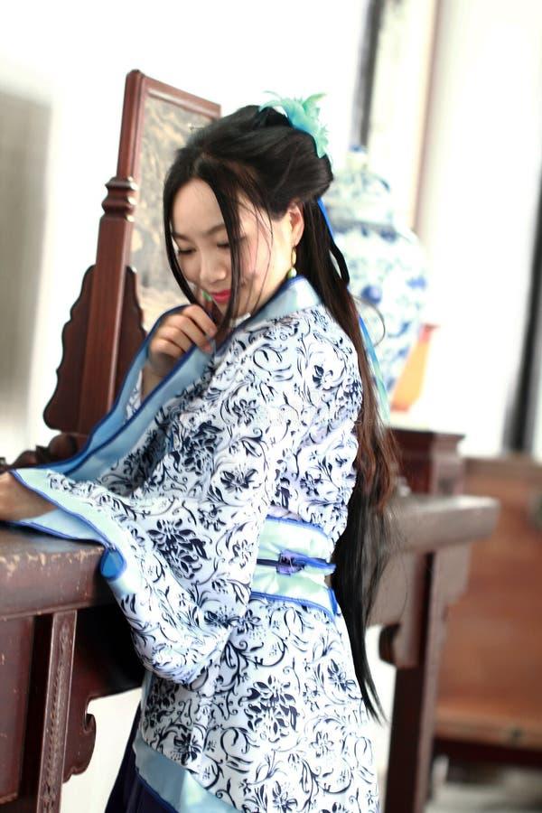 Aisan Chińska kobieta w tradycyjnej Błękitnej i białej Hanfu sukni, stał bezczynnie antycznego stół zdjęcie royalty free