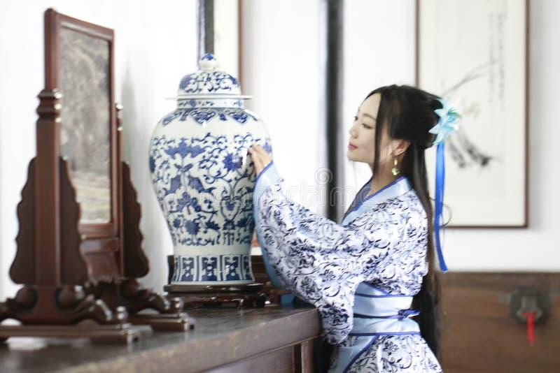 Aisan Chińska kobieta w tradycyjnej Błękitnej i białej Hanfu sukni, stał bezczynnie antycznego stół obraz royalty free
