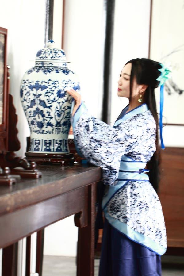 Aisan Chińska kobieta w tradycyjnej Błękitnej i białej Hanfu sukni, stał bezczynnie antycznego stół zdjęcia royalty free