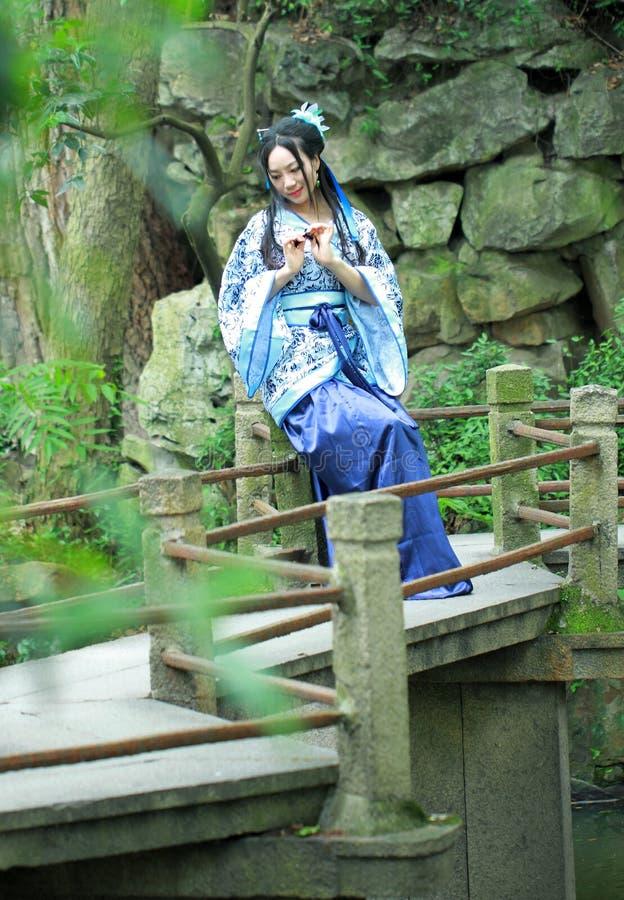 Aisan Chińska kobieta w tradycyjnej Błękitnej i białej Hanfu sukni, sztuka w ogródzie zdjęcia stock