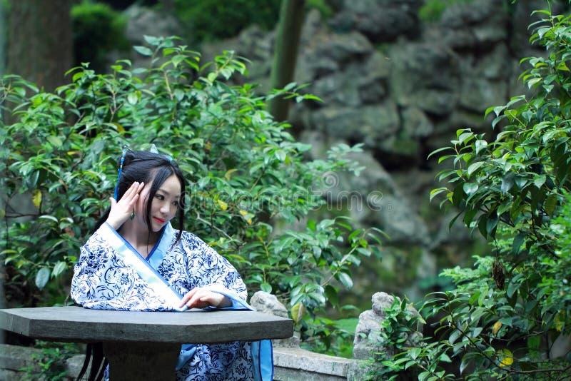 Aisan Chińska kobieta w tradycyjnej Błękitnej i białej Hanfu sukni, zwłoka czas w sławnym ogródzie obraz royalty free