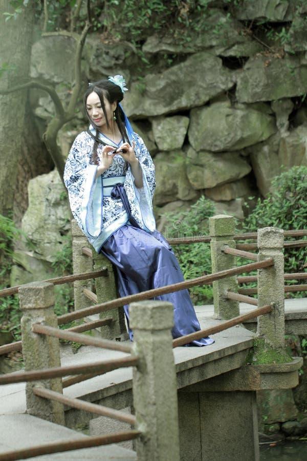 Aisan Chińska kobieta w tradycyjnej Błękitnej i białej Hanfu sukni, zwłoka czas w sławnym ogródzie zdjęcia royalty free