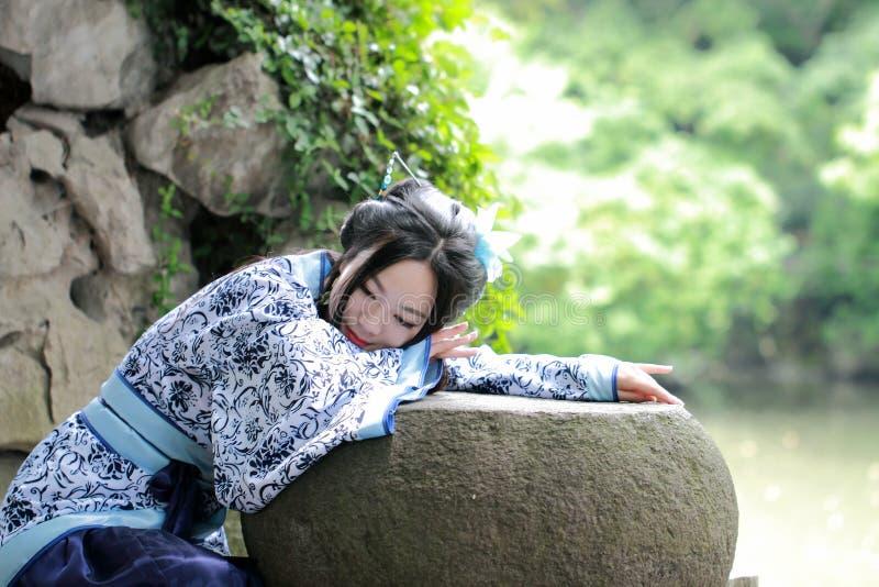 Aisan Chińska kobieta w tradycyjnej Błękitnej i białej Hanfu sukni, zwłoka czas w sławnym ogródzie obrazy stock