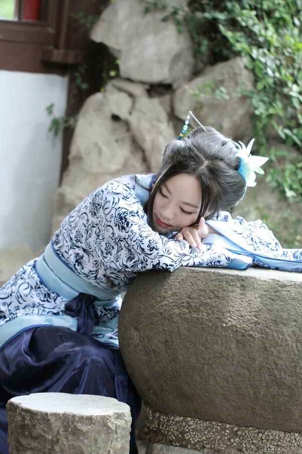 Aisan Chińska kobieta w tradycyjnej Błękitnej i białej Hanfu sukni, zwłoka czas w sławnym ogródzie zdjęcie stock