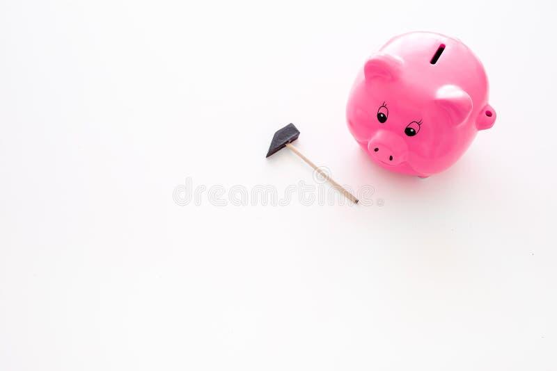 Aislado en blanco Moneybox en la forma del cerdo cerca del martillo en el espacio blanco de la copia del fondo fotografía de archivo libre de regalías
