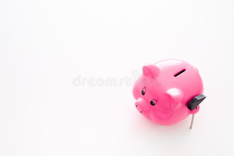 Aislado en blanco Moneybox en la forma del cerdo cerca del martillo en el espacio blanco de la copia del fondo fotos de archivo libres de regalías