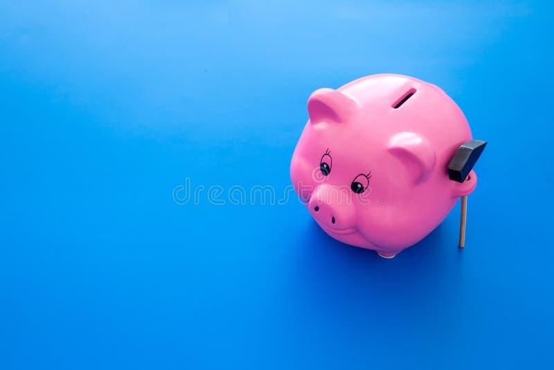 Aislado en blanco Moneybox en la forma del cerdo cerca del martillo en espacio azul de la copia del fondo foto de archivo