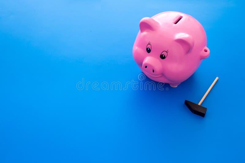 Aislado en blanco Moneybox en la forma del cerdo cerca del martillo en espacio azul de la copia del fondo imagen de archivo
