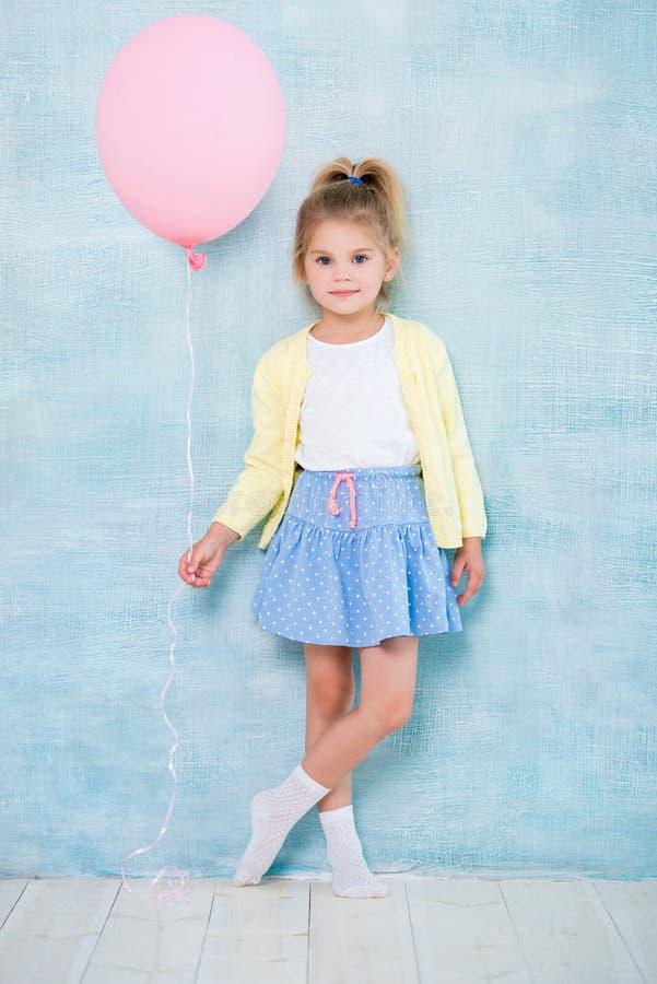 Aislado en el fondo blanco Niña linda que sostiene un globo rosado en un fondo azul imagenes de archivo