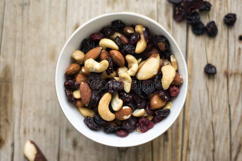 Aislado poco cuenco blanco de nueces mezcladas y de frutas secadas en el fondo rústico foto de archivo libre de regalías