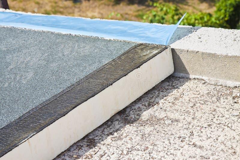 Aislamiento térmico del tejado con los paneles del poliestireno cubiertos con la membrana impermeable bajo perorata concreta - im foto de archivo libre de regalías