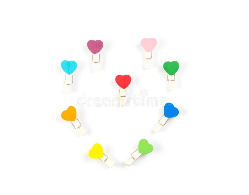 Aislante determinado del corazón colorido de madera del clip de papel de la visión superior en b blanco foto de archivo libre de regalías