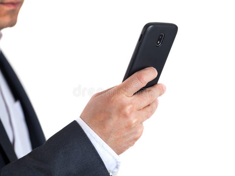 Aislante móvil del negro del uso del hombre de negocios en el fondo blanco foto de archivo libre de regalías