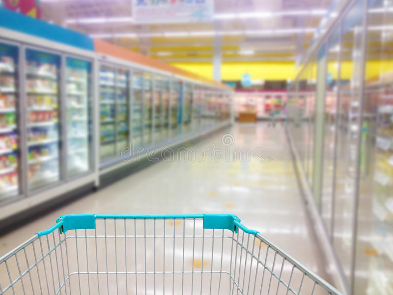 Aisle Milk Yogurt Frozen Food Freezer and Shelves in supermarket. Shopping cart view in Supermarket Aisle Milk Yogurt Frozen Food Freezer and Shelves blurred royalty free stock photography