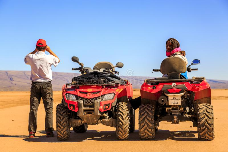 Ait Saoun,摩洛哥- 2016年2月22日:坐在多虫的汽车的夫妇在沙漠 库存照片
