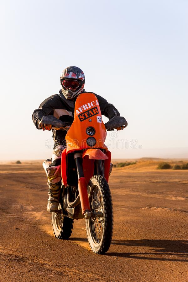 Ait Saoun, Марокко - 22-ое февраля 2016: гонщик на мотоцикле в летнем дне пустыни стоковые изображения rf