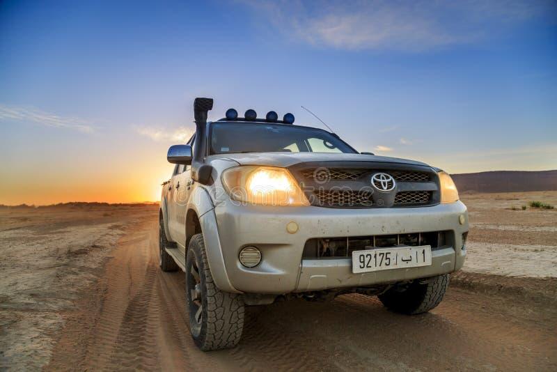 Ait Saoun, Марокко - 23-ье февраля 2016: Тойота Hilux на пустыне во время захода солнца стоковое изображение rf