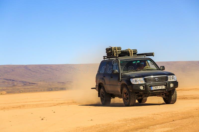 Ait Saoun, Marrocos - 22 de fevereiro de 2016: Homem que conduz o cruzador da terra de toyota no deserto fotos de stock