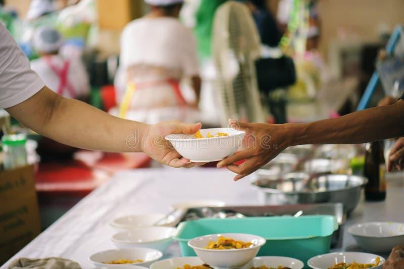 Aiutando il povero nella società donando alimento: Il concetto di fame fotografia stock