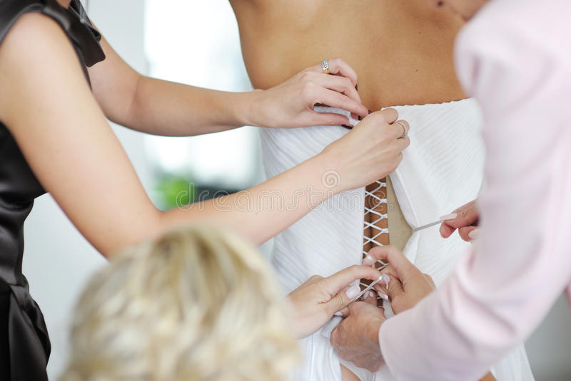 Aiutando una sposa a mettere il suo vestito da cerimonia nuziale sopra immagine stock libera da diritti