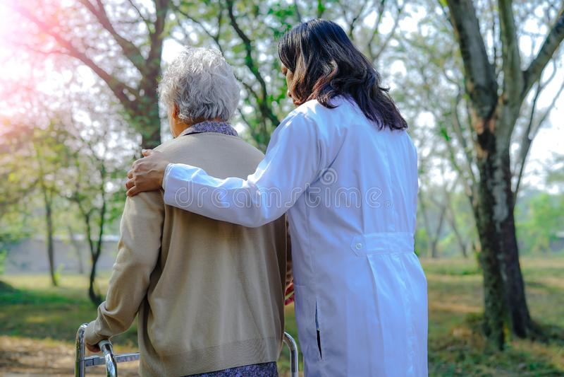 Aiuti e preoccupi il camminatore senior o anziano asiatico di uso della donna della signora anziana con forte salute mentre cammi fotografia stock libera da diritti