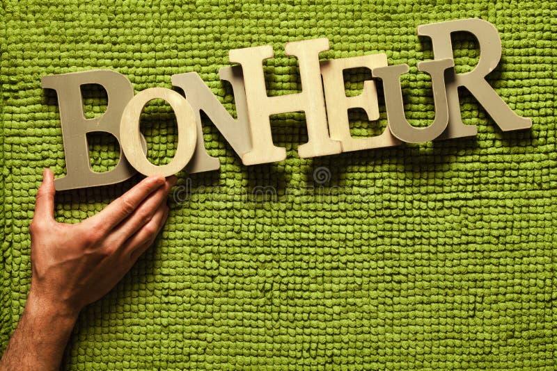 Aiuto di felicità (Bonheur) su a mano Fondo dell'erba verde fotografia stock