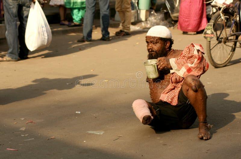 Aiuto di ricerca del mendicante malato indiano su una strada di grande traffico fotografia stock libera da diritti