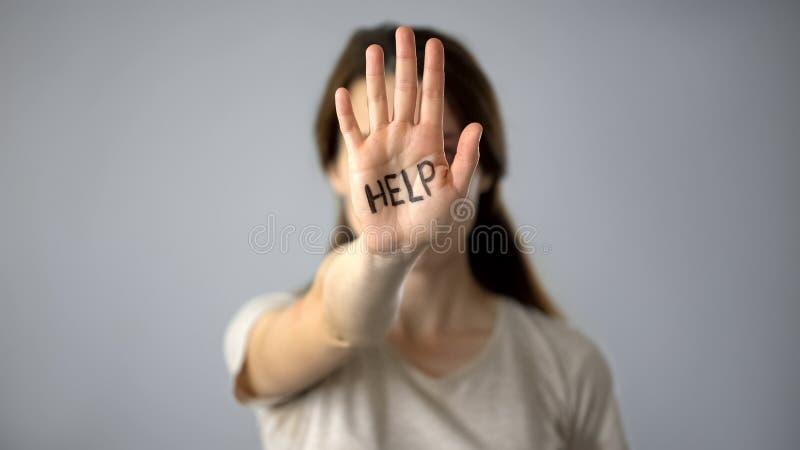 Aiuto scritto sulla mano della donna, traffico umano, trattamento crudele, aggressione sessuale fotografia stock