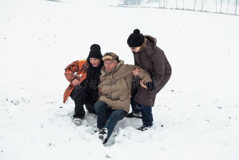 Aiuto senior di incidente e della gente della neve fotografia stock