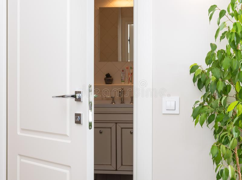 Ajar white door in a dark bathroom. Series switch on a light gray wall. Modern chrome door handle and lock stock photo