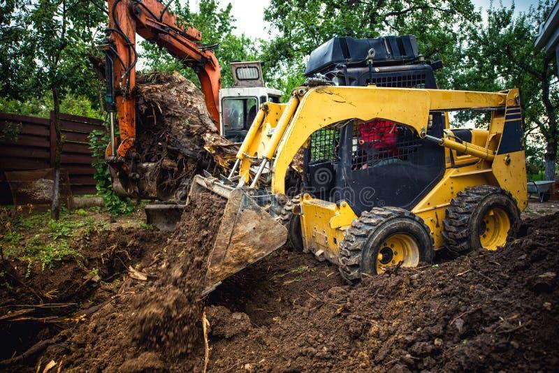Ajardinar trabalha com o canteiro de obras da escavadora e da máquina escavadora em casa fotografia de stock royalty free