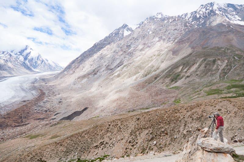 Ajardine al fotógrafo que tira un glaciar, trabajando en montaña de Himalaya fotografía de archivo libre de regalías