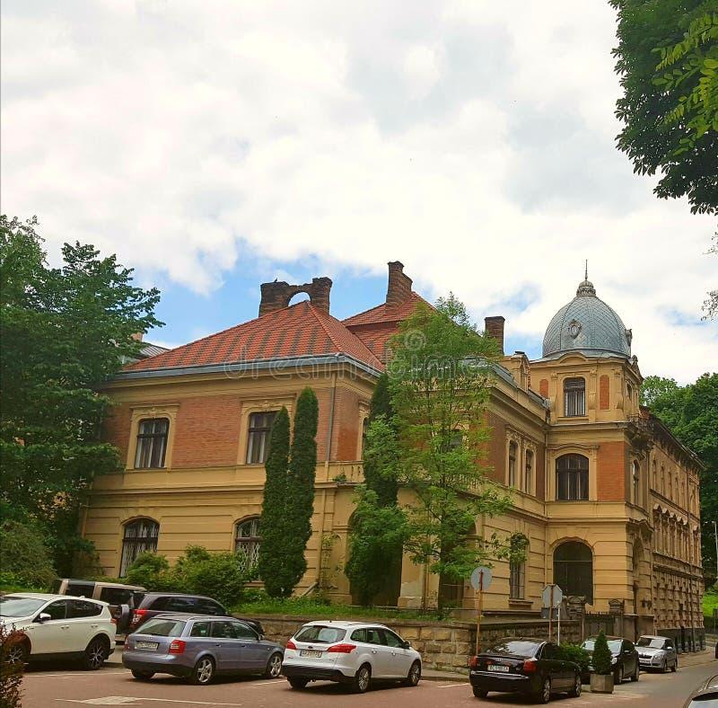 Ajardine a casa, uma construção de tijolo com um telhado vermelho e uma abóbada Em torno de muitos carros e árvores cresça O céu  imagens de stock