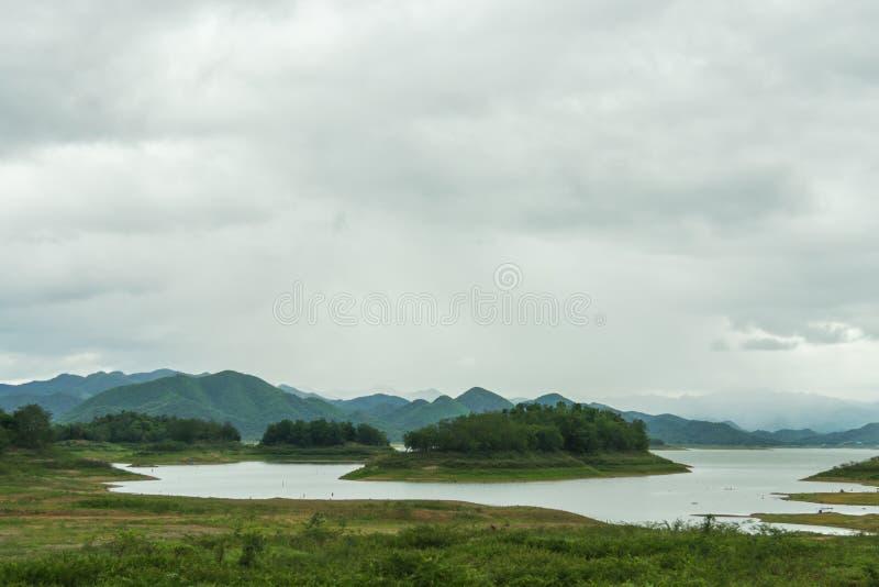Ajardine com árvores das montanhas e um rio na parte dianteira imagem de stock