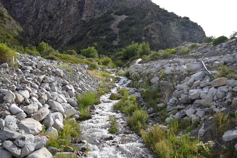 Ajardine com montanhas e um rio na parte dianteira Cen?rio bonito foto de stock royalty free