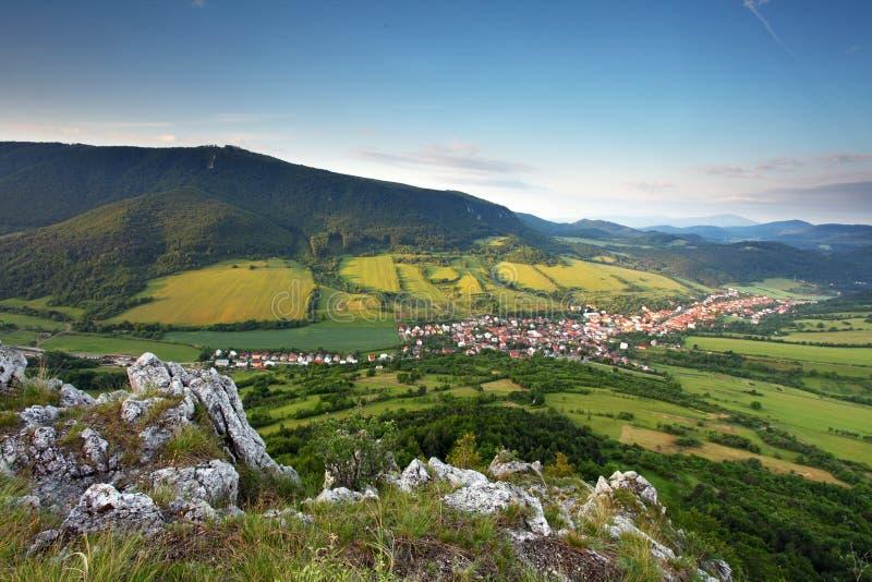 Ajardine con la aldea, las montañas y el cielo azul imagenes de archivo