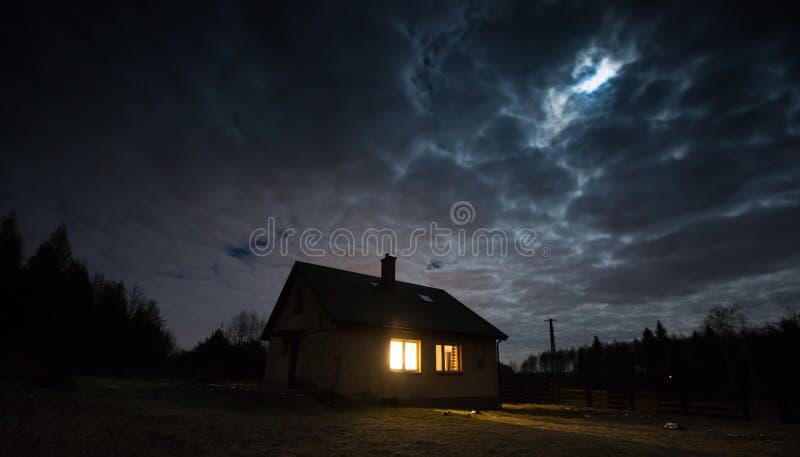 Ajardine con la casa en la noche debajo del cielo nublado fotos de archivo