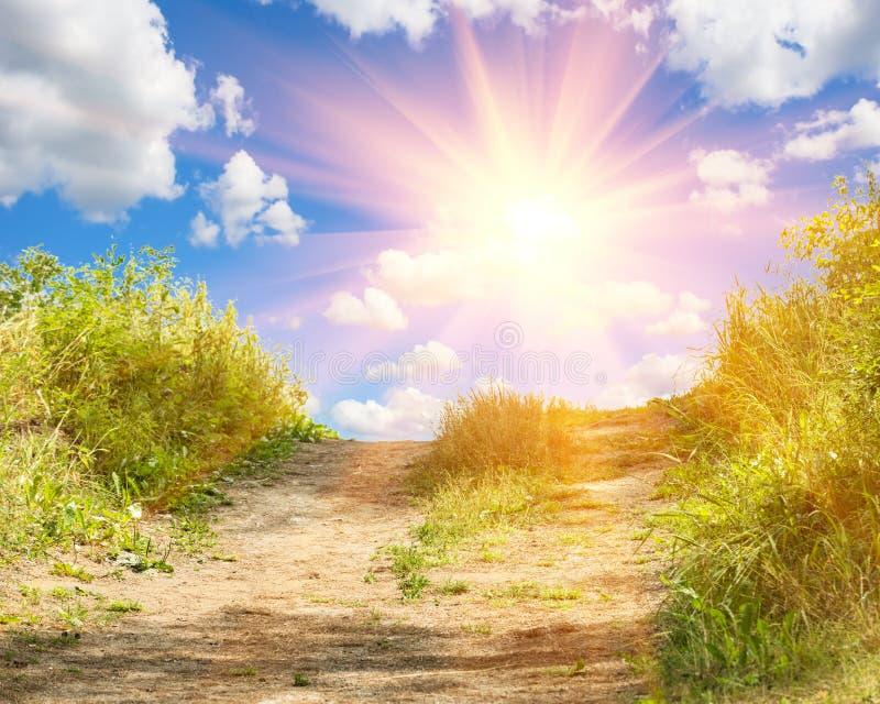 Ajardine con la hierba verde, el camino y las nubes fotos de archivo