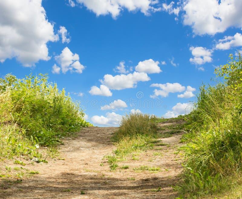 Ajardine con la hierba verde, el camino y las nubes foto de archivo