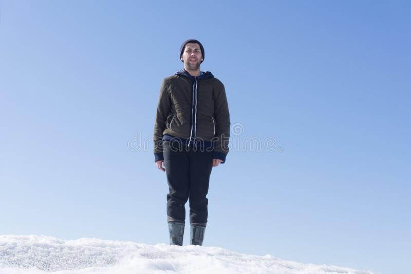 Ajardine con la silueta de un hombre feliz derecho con la mochila y los brazos aumentados-para arriba en el pico de montaña en el imagenes de archivo