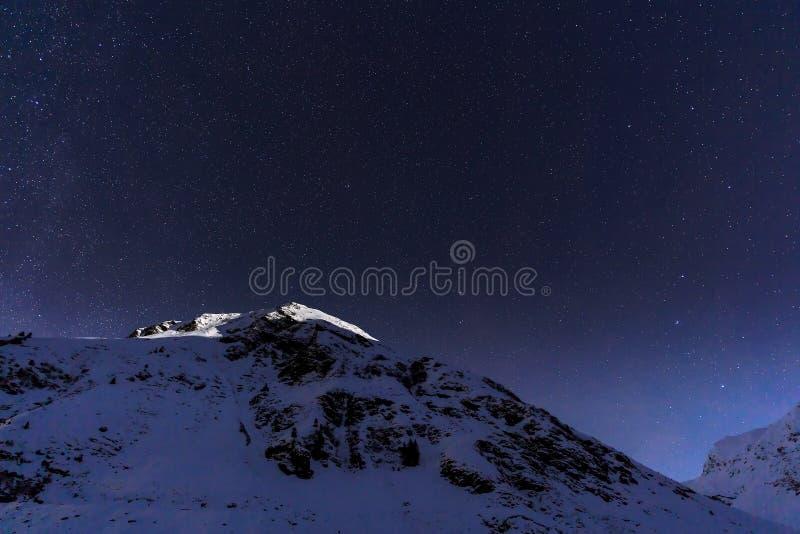Ajardine con las montañas y el cielo azul en noche del invierno imágenes de archivo libres de regalías