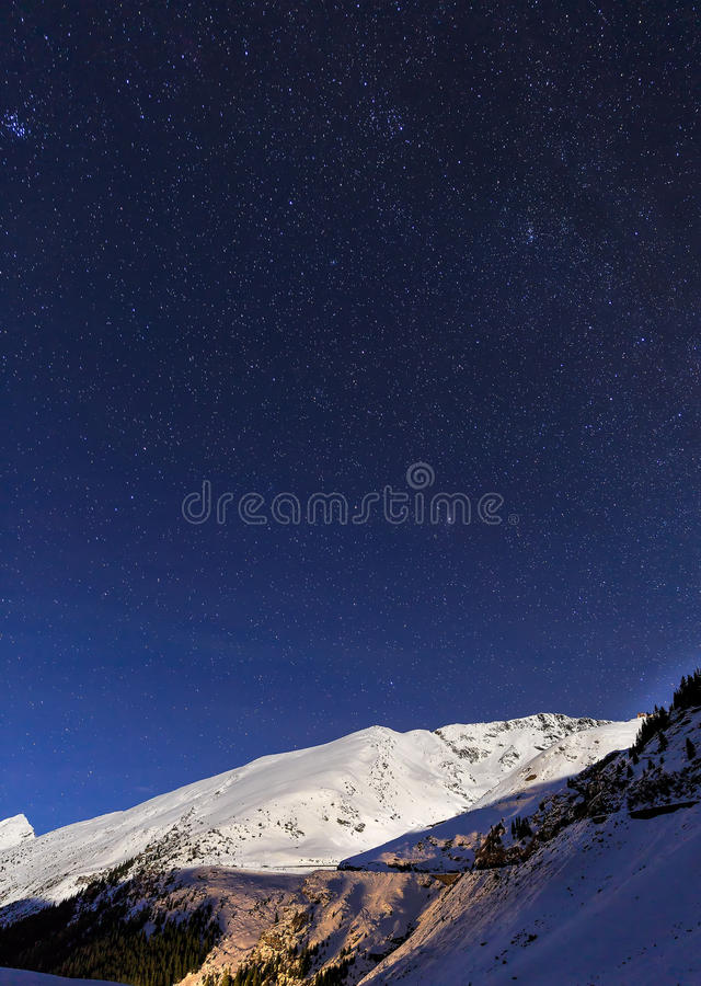 Ajardine con las montañas y el cielo azul en noche del invierno fotos de archivo libres de regalías