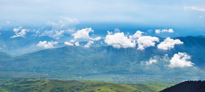 Ajardine con las nubes, las montañas, el cielo azul y el pueblo Carpathi imágenes de archivo libres de regalías