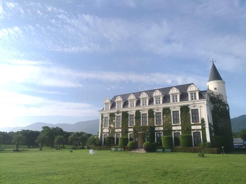 Ajardine el edificio del vintage y cielo azul y montaña imagen de archivo