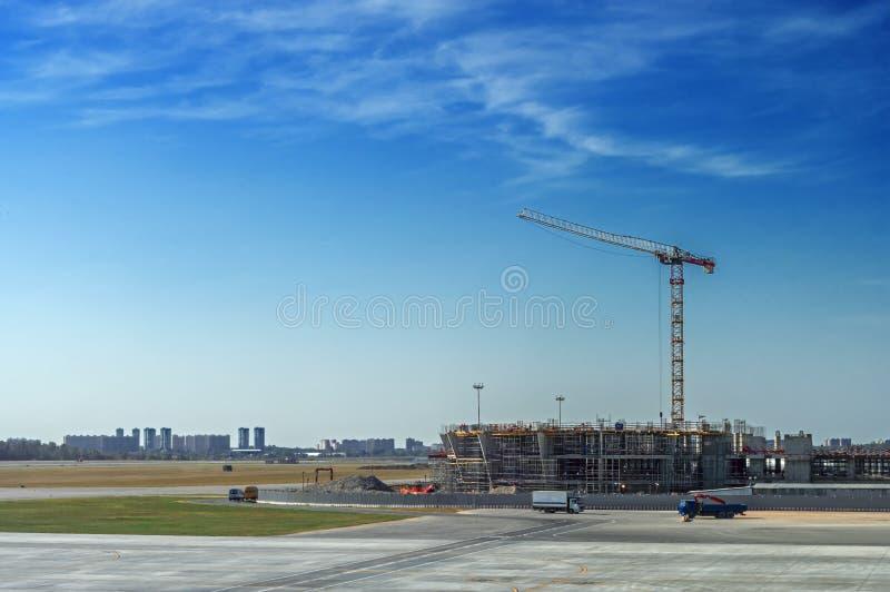 Ajardine el emplazamiento de la obra grande con la grúa de construcción grande en fondo del cielo azul el día de verano fotografía de archivo
