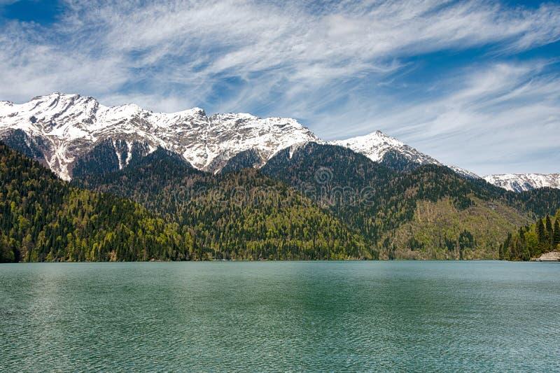 Ajardine el lago en un fondo de montañas y de nubes blancas Día asoleado foto de archivo libre de regalías