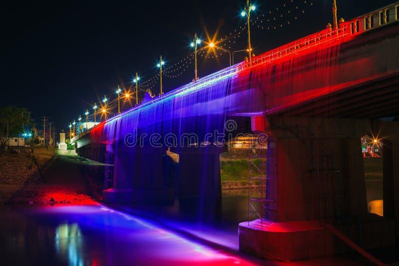 Ajardine el puente de Naresuan y la cascada ligera en la noche en Phisan foto de archivo