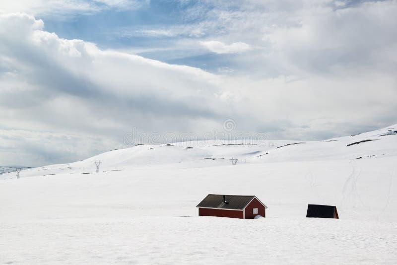 Ajardine en el día de verano soleado con nieve y casas solas, en el camino Aurlandsfjellet, Noruega fotos de archivo