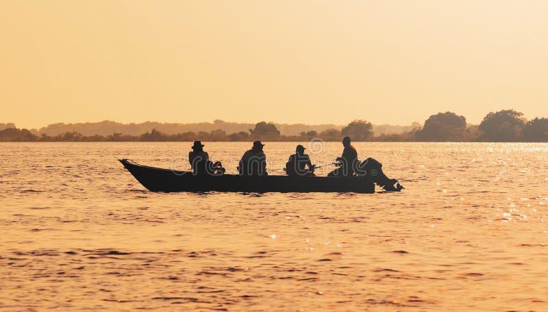 Ajardine en la puesta del sol de un barco con los pescadores que pescan en Pantanal fotografía de archivo
