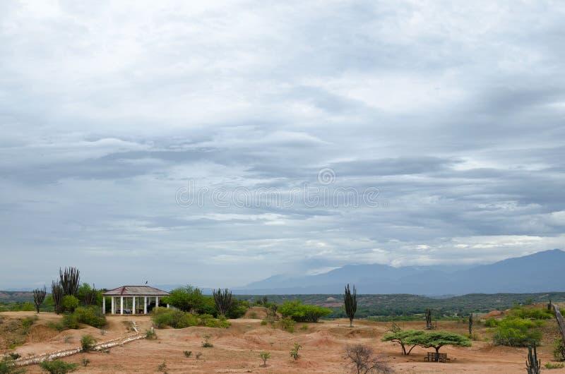 Ajardine en pradera debajo del cielo nublado con un refugio fotos de archivo libres de regalías